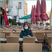 Coface Focus on Germany: More insolvencies in the pipeline. The photo shows a woman wearing a mask sitting alone on a café terrace in Cologne, Germany.